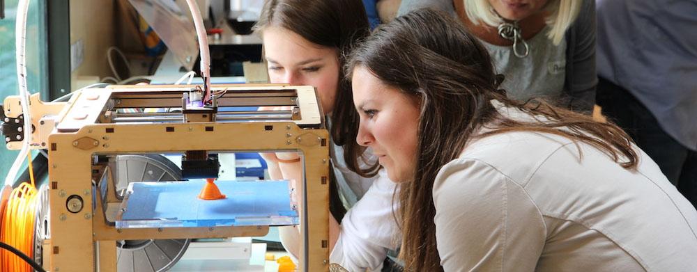 Das Foto zeigt zwei Frauen, die um einen 3D-Drucker stehen und zusehen, wie der Drucker arbeitet.