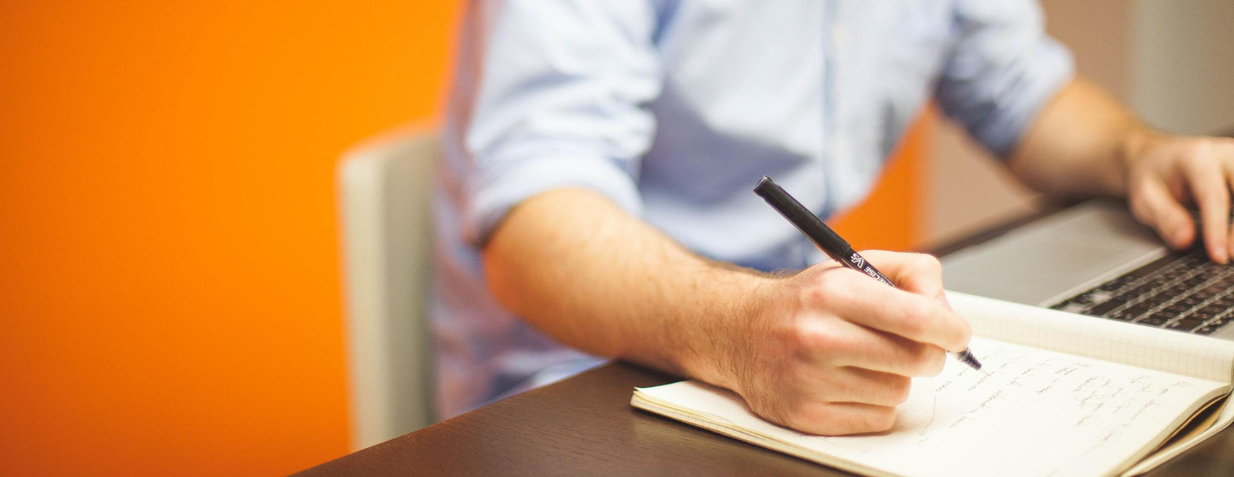 Das Foto zeigt einen Mann, der am Tisch sitzt, mit einem Laptop arbeitet und gleichzeitig Notizen macht.