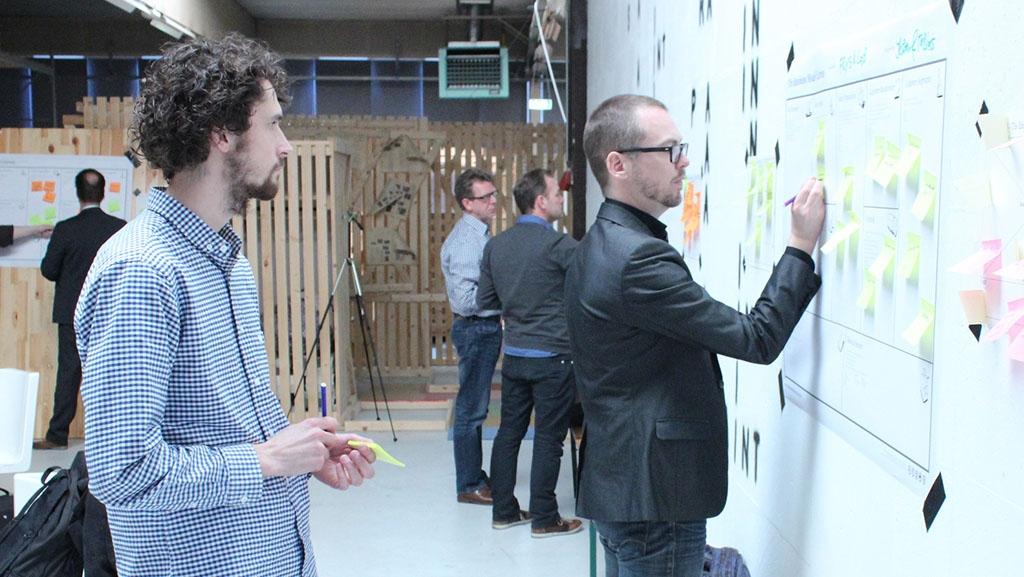 Das Bild zeigt vier Personen an einer Planwand. Eine Person schreibt eine Notiz auf einen Haftzettel an der Wand und wird dabei von einer weiteren Person beobachtet.