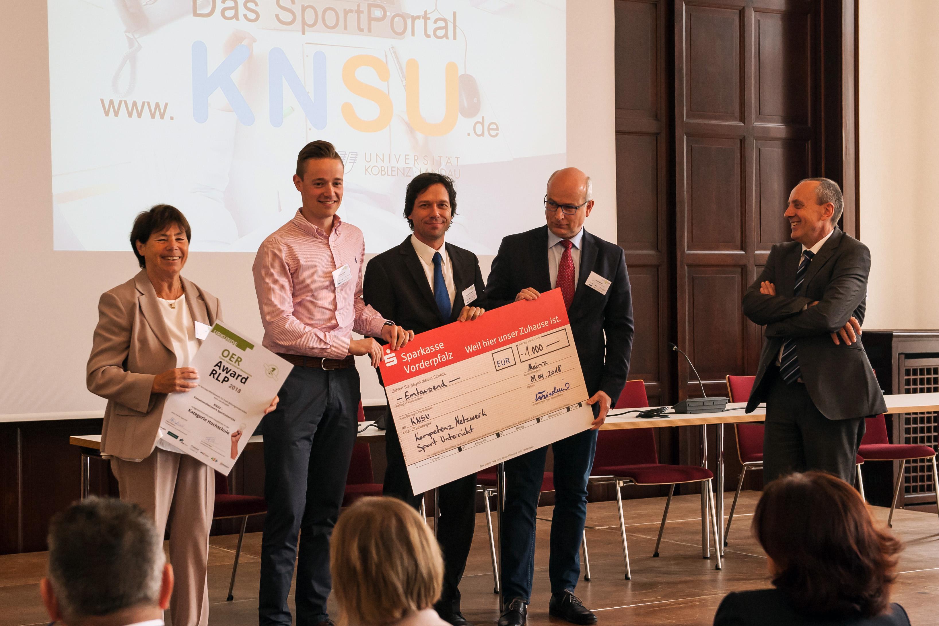"""Das Foto zeigt die Gewinner*innen des OER Awards RLP 2018 im Bereich """"Hochschulbildung"""" bei der Siegerehrung zusammen mit Minister Konrad Wolf."""